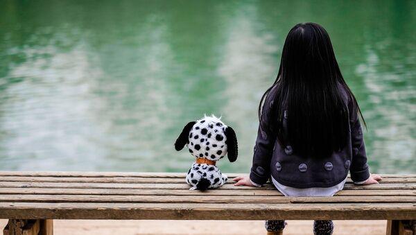 Маленькая девочка сидит на скамейке, архивное фото - Sputnik Тоҷикистон