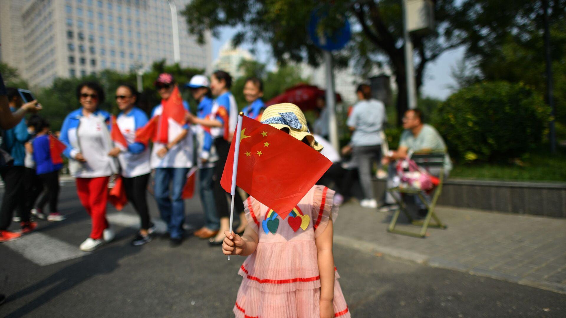 Девочка с китайским флагом на военном параде в честь 70-летия образования КНР в Пекине - Sputnik Тоҷикистон, 1920, 19.04.2021