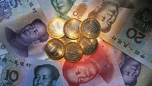 Китайские банкноты номиналом в 100, 50, 20, 10 и 5 юаней и российские 10 рублевые монеты, архивное фото - Sputnik Таджикистан
