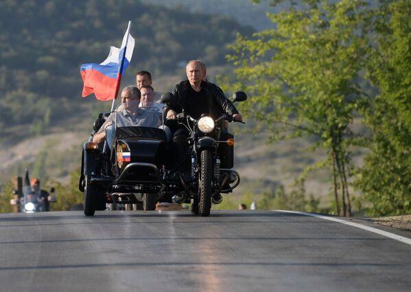 Президент РФ Владимир Путин участвует в организованном мотоклубом Ночные волки международном байк-шоу Тень Вавилона в Севастополе за рулем мотоцикла Урал  - Sputnik Таджикистан