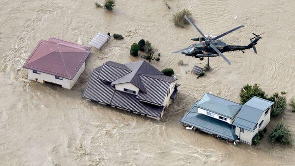 Вертолет над жилыми районами, затопленными рекой Чикума после тайфуна Хагибис в Нагано, центральная Япония - Sputnik Тоҷикистон