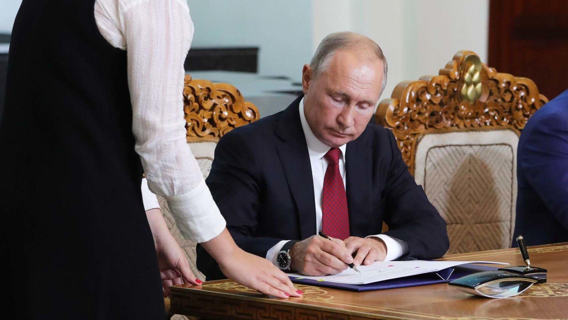 Президент РФ Владимир Путин подписывает документ, архивное фото - Sputnik Таджикистан, 1920, 01.07.2021