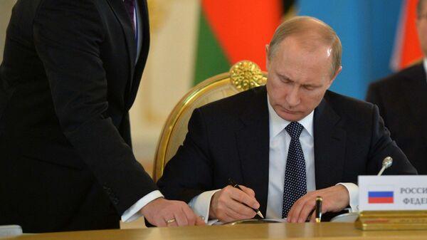 Президент РФ Владимир Путин подписывает документ, архивное фото - Sputnik Тоҷикистон