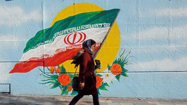 Женщина в Тегеране на фоне рисунка флага на стене - Sputnik Тоҷикистон