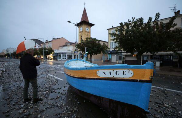 Человек у лодки после наводнения в Кань-Сюр-Мер, Франция - Sputnik Таджикистан