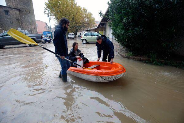 Люди в надувной лодке на одной из улиц Лемю на юго-востоке Франции после наводнения - Sputnik Таджикистан
