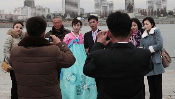 Молодожены во время свадебной фотосессии со своими родственниками в Пхеньяне - Sputnik Таджикистан