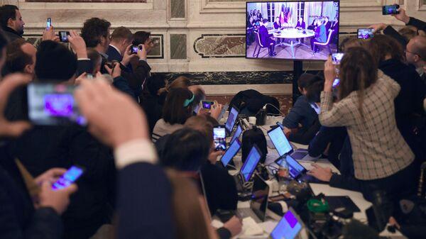 Журналисты смотрят трансляцию встречи глав государств-участников Нормандского формата в Елисейском дворце - Sputnik Тоҷикистон