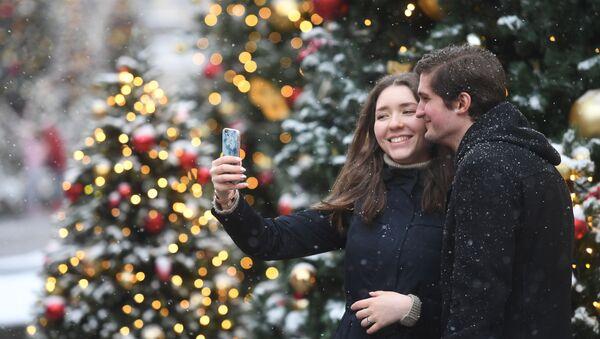 Молодые люди фотографируются во время снегопада в Москве - Sputnik Таджикистан