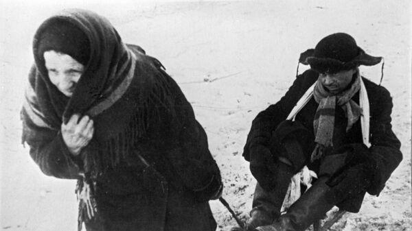 Женщина везет ослабевшего от голода мужа в дни блокады Ленинграда - Sputnik Таджикистан