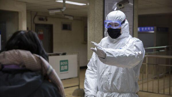 Работник, в защитном костюме, жестами обращается к пассажиру на станции метро в Пекине - Sputnik Тоҷикистон