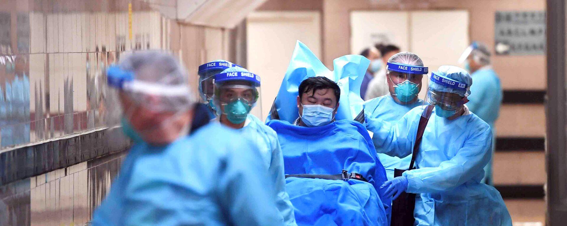Медицинский персонал переводит пациента с подозрением на новый коронавирус, в Гонконге - Sputnik Таджикистан, 1920, 21.06.2020