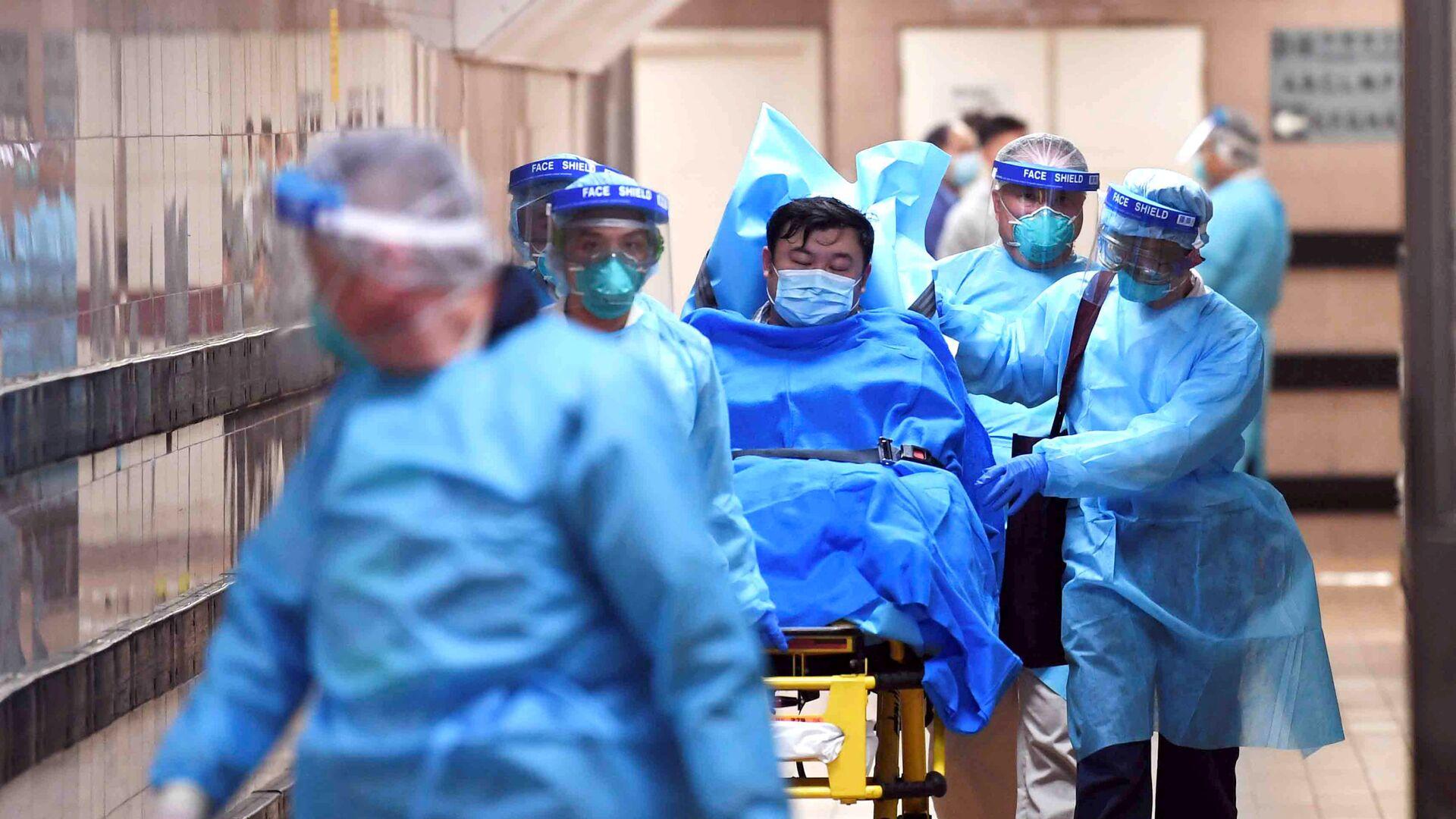 Медицинский персонал переводит пациента с подозрением на новый коронавирус, в Гонконге - Sputnik Таджикистан, 1920, 18.06.2021