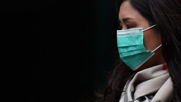 Девушка в медицинской маске в районе Чайна-таун в Лондоне - Sputnik Тоҷикистон