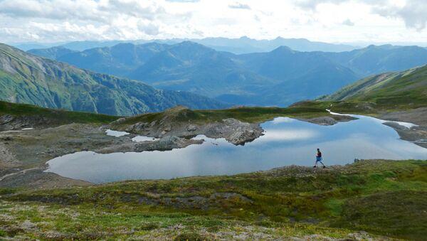 Путешественник проходит мимо горного водоема на Аляске - Sputnik Таджикистан