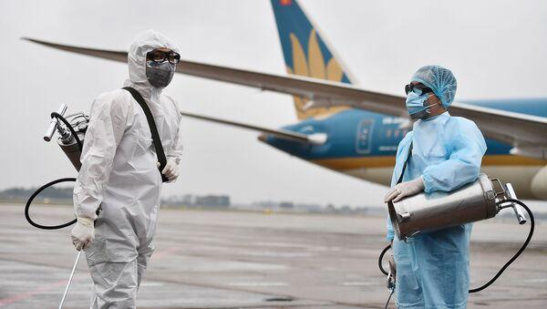 Сотрудники в защитных костюмах готовятся к дезинфекции самолета - Sputnik Тоҷикистон