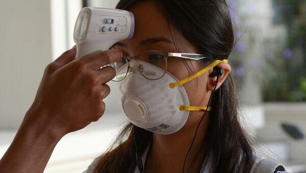 Студентке в защитной лицевой маске измеряют температуру - Sputnik Таджикистан