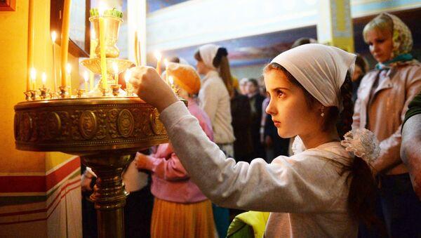 Девочка ставит свечку в православном храме, архивное фото - Sputnik Таджикистан