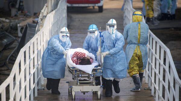 Медицинские работники в защитных костюмах перевозят пациентов, архивное фото - Sputnik Таджикистан