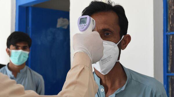 Врач проверяет температуру тела мужчины, возвращающегося из Ирана в карантинную зону, для проверки на коронавирус COVID-19 - Sputnik Тоҷикистон