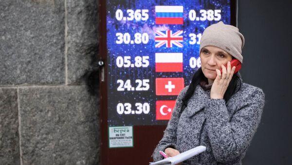 Женщина около пункта обмена валют в Киеве - Sputnik Таджикистан
