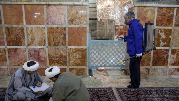 Работник санитарной службы дезинфицирует Мавзолей Фатимы Масуме в иранском городе Кум - Sputnik Тоҷикистон