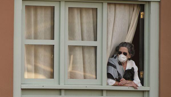 Женщина смотрит из окна Costa Adeje Palace hotel на Тенерифе - Sputnik Тоҷикистон