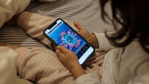 Маленькая девочка смотрит на иллюстрацию коронавируса на экране смартфона, Италия - Sputnik Тоҷикистон