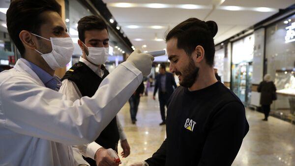 Медработники проверяют посетителя торгового центра в Тегеране на фоне вспышки коронавируса - Sputnik Тоҷикистон
