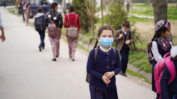 Школьница в медицинской маске на улице Душанбе - Sputnik Тоҷикистон