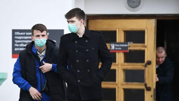 Пассажиры в медицинских масках у входа в железнодорожный вокзал - Sputnik Тоҷикистон