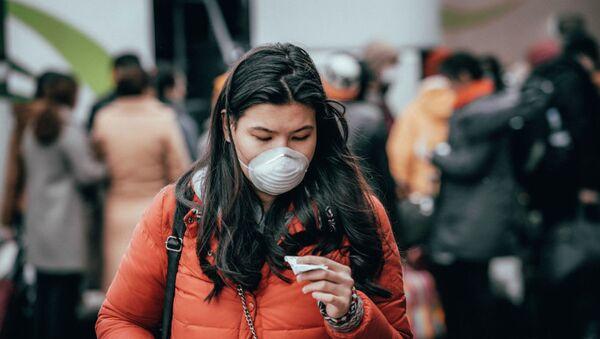 Девушка в маске на автовокзале в Нур-Султане накануне карантина  - Sputnik Тоҷикистон