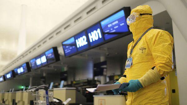 Работник в защитном костюме в аэропорту Уханя - Sputnik Тоҷикистон