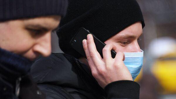 Молодой человек в медицинской маске разговаривает по телефону - Sputnik Таджикистан