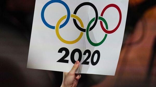 Журналист держит плакат с олимпийскими кольцами  - Sputnik Тоҷикистон