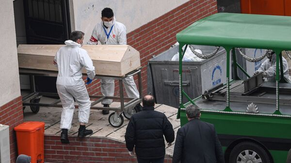 Должностные лица в масках погружают гроб в транспортное средство - Sputnik Тоҷикистон