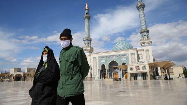 Пара в защитных пасках на улице в иранском городе Кум - Sputnik Тоҷикистон
