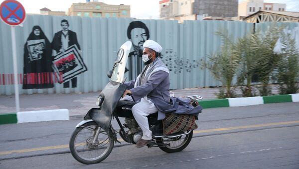 Мужчина в защитной маске едет на мотоцикле по улице в Иране - Sputnik Тоҷикистон