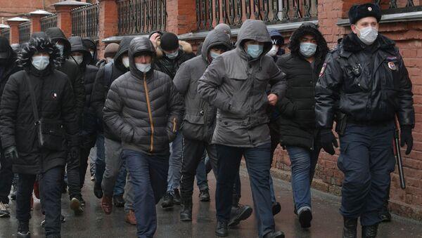 Сотрудник полиции выстраивает в очередь мигрантов - Sputnik Тоҷикистон