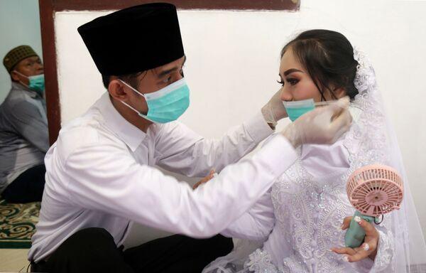 Жених и невеста в масках в Джакарте  - Sputnik Таджикистан