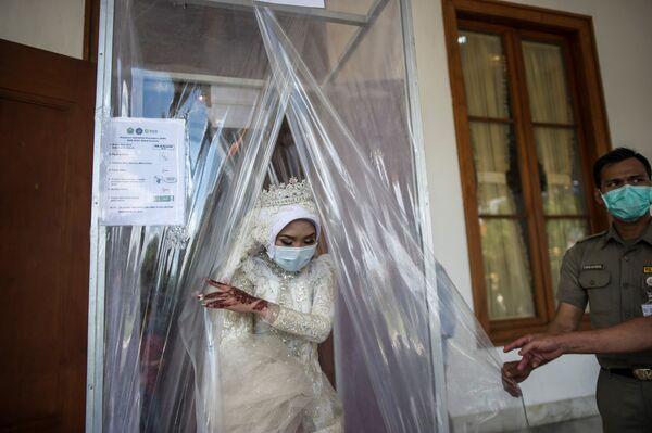 Индонезийская невеста в маске после дезинфекции во время свадебной церемонии в городе Сурабая - Sputnik Таджикистан
