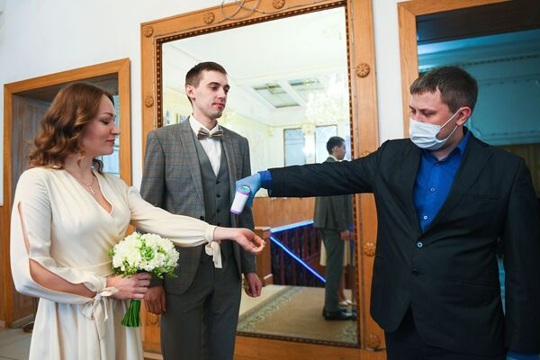 Сотрудник ЗАГСа проверяет температуру у молодоженов перед заключением брака во дворце бракосочетания №1 в Москве - Sputnik Таджикистан