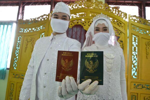 Молодожены со свадебными сертификатами в Джакарте  - Sputnik Таджикистан