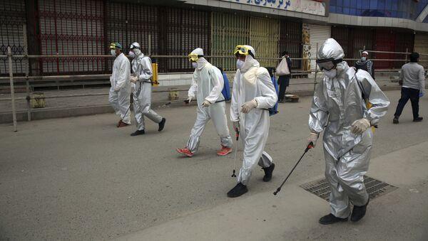 Добровольцы в защитных костюмах распыляют дезинфицирующее средство против распространение коронавируса в Кабуле - Sputnik Тоҷикистон