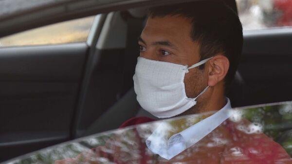 Водитель автомобиля в защитной медицинской маске - Sputnik Таджикистан