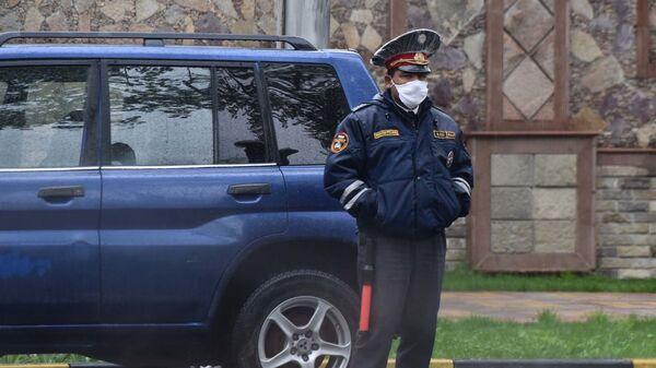 Сотрудник милиции в защитной медицинской маске - Sputnik Таджикистан