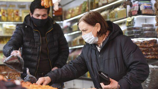 Женщина в медицинской маске выбирает товар на рынке - Sputnik Таджикистан