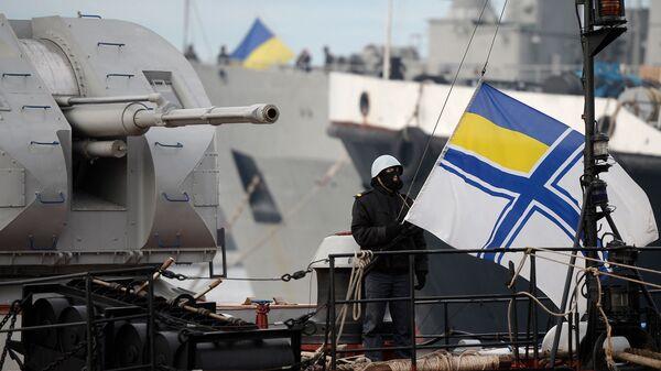 Украинский солдат поднимает флаг украинского военно-морского флота, стоя на страже на борту военного корабля - Sputnik Таджикистан