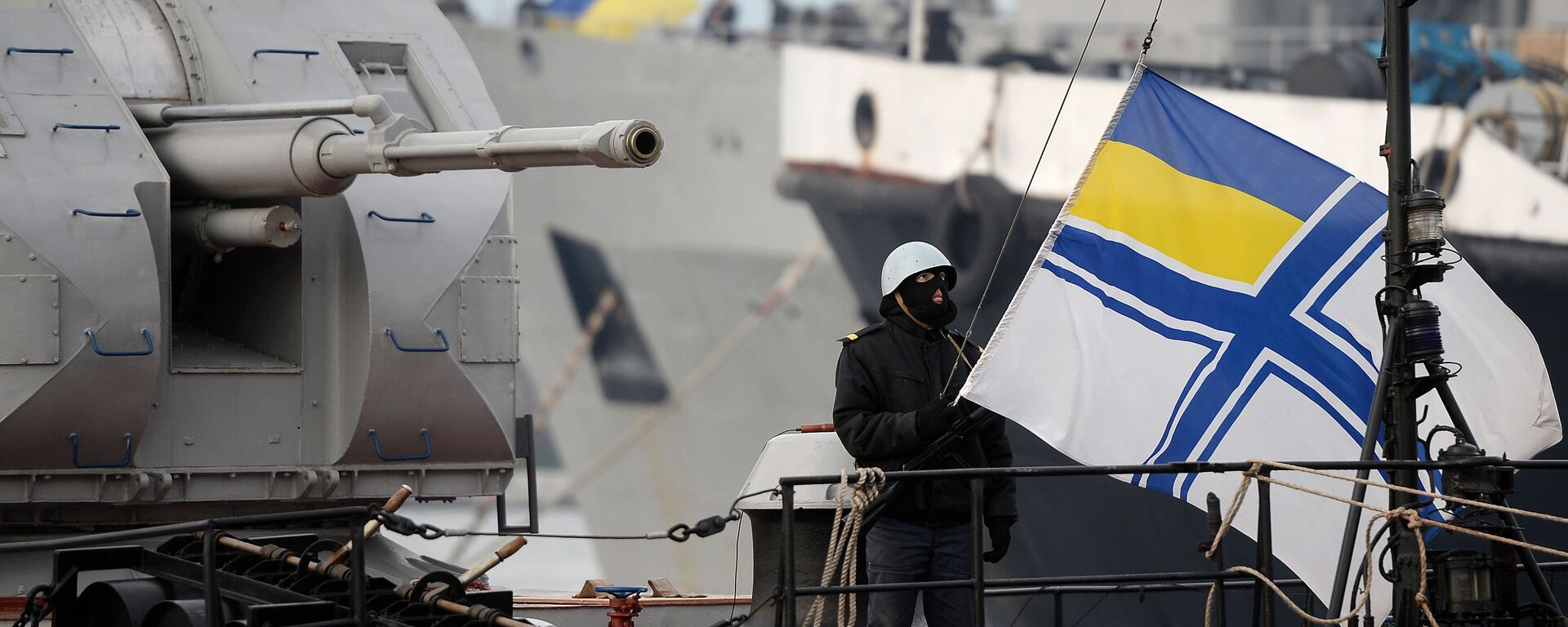 Украинский солдат поднимает флаг украинского военно-морского флота, стоя на страже на борту военного корабля - Sputnik Таджикистан, 1920, 08.04.2021