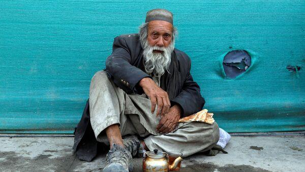 Бездомный мужчина пьет чай в придорожном чайном магазине в Кабуле, Афганистан - Sputnik Тоҷикистон